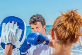 Couple training boxing on the beach - fitness training