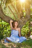 Lovely young lady wearing elegant white dress relaxing in the forest