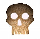 image of wheat-free  - Skull shaped piece of bread cut from whole wheat loaf to illustrate danger from gluten in wheat products - JPG