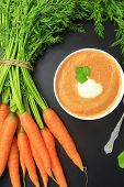 Fresh carrots with leaves and soup on blackboard