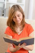 Young woman student reading a book in home
