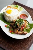 stock photo of crispy rice  - Traditional Thai dish crispy pork with a fried egg atop the jasmine rice served with chili sauce - JPG