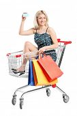 Young woman driving in a shopping cart isolated on white background