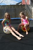 Children jumping on a trampoline in summer in there back yard