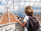 Boy looking through a sightseeing binoculars the Dome of Basilica di Santa Maria del Fiore (Saint Ma