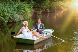 stock photo of married  - beautiful young wedding couple blonde bride with flower and her groom just married on small boat at pond with evening sun - JPG