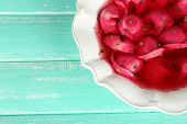 Traditional polish clear red borscht with dumplings on color wooden background