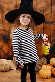Little witch girl in hat asks candy on Halloween decorations background