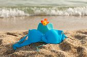 Turquoise Summer Hat, Bikini And Flower On The Beach