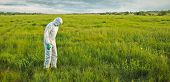 Scientist In Protective Uniform On Summer Field