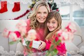 Little girl giving her mother a christmas gift against snowflake frame