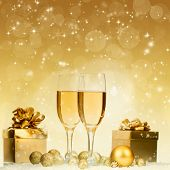 Glasses with champagne and gift box against holiday lights