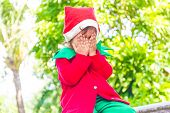 young happy child dressed as santa helper elf, xmas costume, green outdoor background