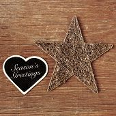 the sentence seasons greetings written in a heart-shaped chalkboard and a rustic christmas star on a wooden surface