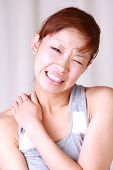 picture of stiff  - young Japanese woman suffers from stiff neck - JPG