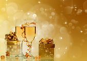 Glasses with champagne and golden gift boxes against holiday lights