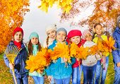 Row of happy kids with rake and leaves bunches