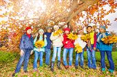 Kids group with bunches of yellow maple leaves