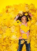 Little African girl covered with autumn leaves