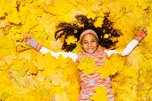 Little African girl under yellow maple leaves