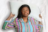 Sleepless African American woman resting head on pillow