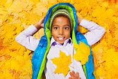 African boy lays in pile of autumn leaves