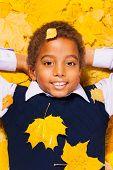 Close portrait of a black boy in autumn leaves