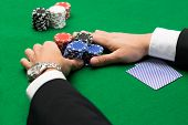 casino, gambling, poker, people and entertainment concept - close up of poker player with playing cards and chips at green casino table