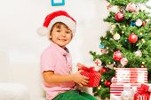 Little boy with present under New year tree