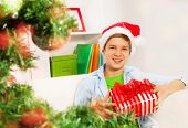 Happy boy with presents near Christmas tree