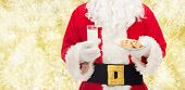 christmas, holidays, food, drink and people concept -close up of santa claus with glass of milk and cookies over yellow lights background