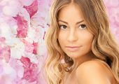 beauty, people and health concept - beautiful young woman with bare shoulders and long wavy hair over pink floral background