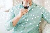 drinks, winery, leisure and people concept - close up of man with glass drinking red wine at home