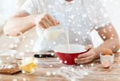 cooking, food, people and home concept - close up of man pouring milk into bowl and other ingredients