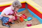 Beautiful Cute Little Girl Playing In Sandbox On Warm Sunny Day