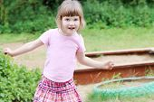 Beautiful Cute Little Girl Standing In Playground Against Background Of Sandbox