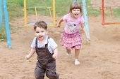 Little Boy In Overalls Runs Away From Girl On Warm Sunny Day