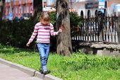 Pretty Happy Girl In Striped Sweater And Jeans Goes On Curb On Sunny Day