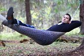 Handsome Young Man Lies In Hammock In Woods At Dull Autumn Day