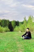 Man Sits On Grass On Edge Of Forest At Autumn Dull Day And Thinks