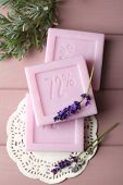 Bars of natural soap with fresh lavender on wooden background