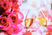 Champagne Flutes With Golden Bubbles On Wedding Roses Flowers Background
