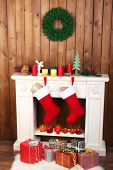 Christmas socks hanging on fireplace in room