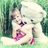 Vintage Photo Of A Girl Sitting In The Grass With Large Teddy Bear