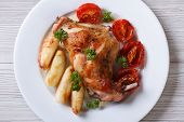 Roasted Rabbit Leg With Apples And Tomatoes On Plate Top View