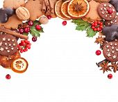 Border frame of christmas cookies , berries , fruits , different xmas ingredients and spices isolated on a white background