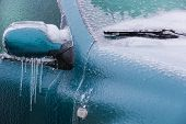 Frozen Rearview Mirror And Wiper Of The Car With Icicles, Ice And Frost