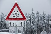 Traffic Sign For Icy Road With Sleet Covered Trees