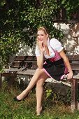 Bavarian blond girl sitting relaxed on a bench in a dirndl.
