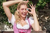 Young woman in dirndl with a praline with white / blue diamond pattern